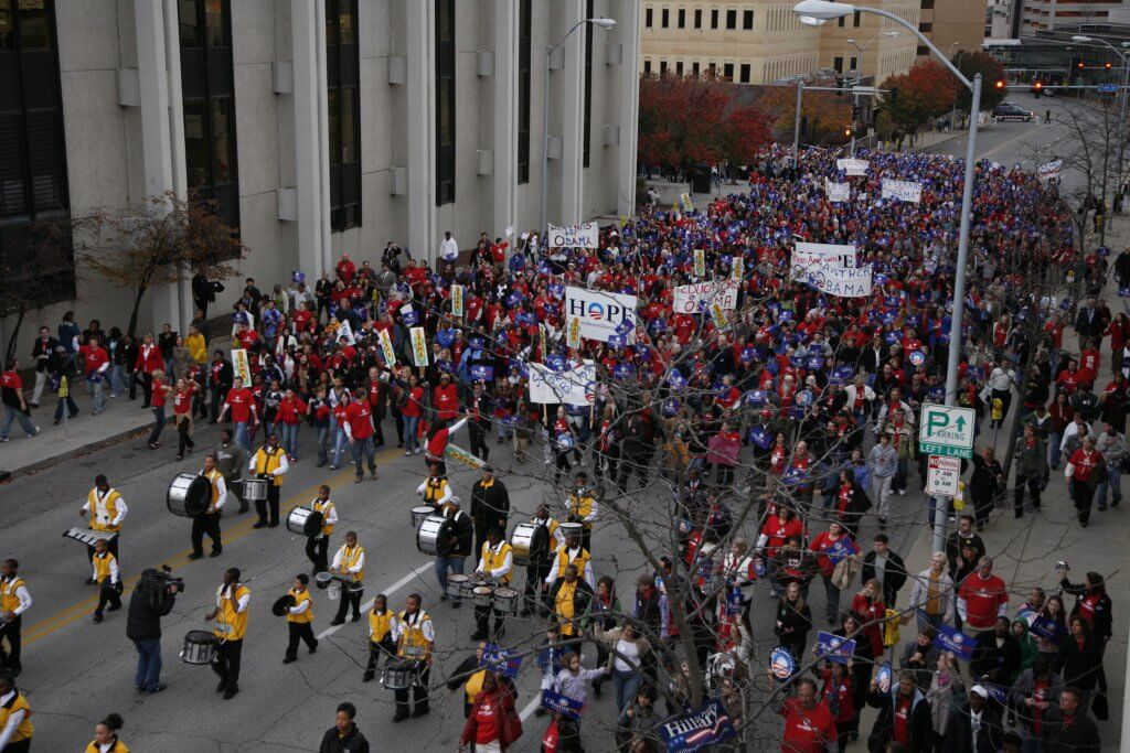 Photo of a crowd of Obama supporters marching through the streets of Des Moines.